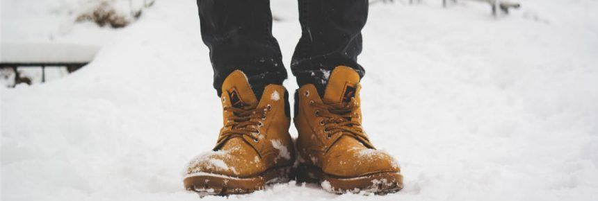 man wearing boots standing in snow